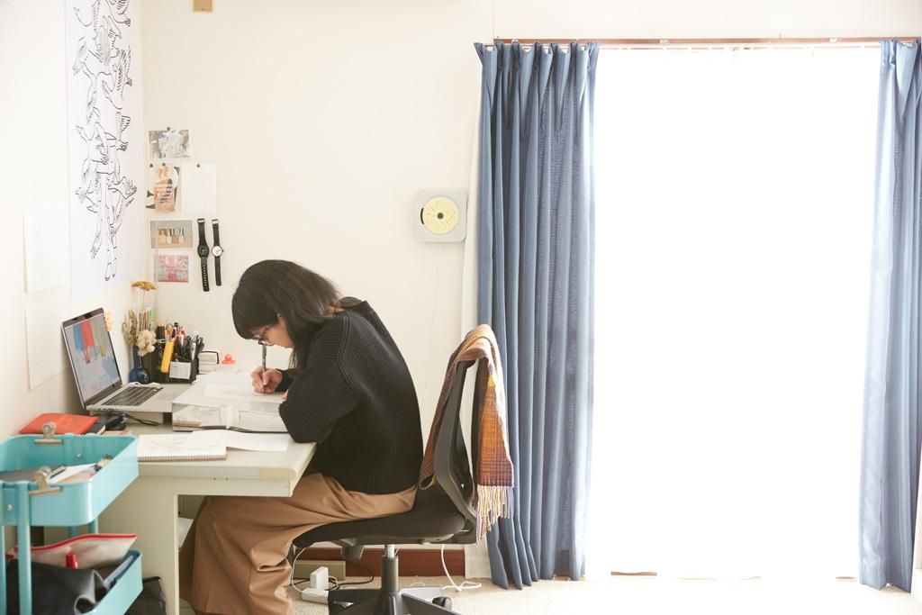 机に向かい仕事をする惣田さんの姿